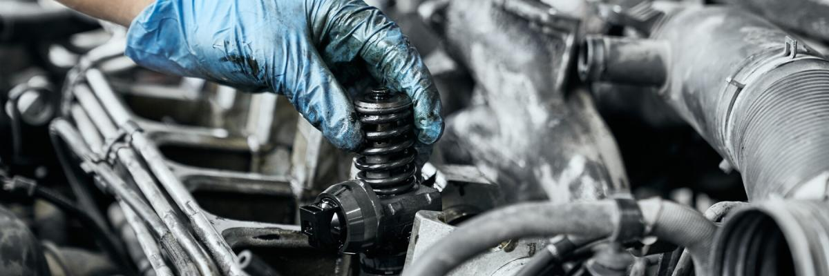 Professional mechanic in dirty protective gloves testing just installed nozzle into diesel car engine. Maintenance and repair concept for diesel engines