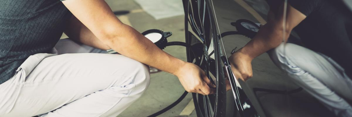 Adult man Checking tire pressure With tire gauge
