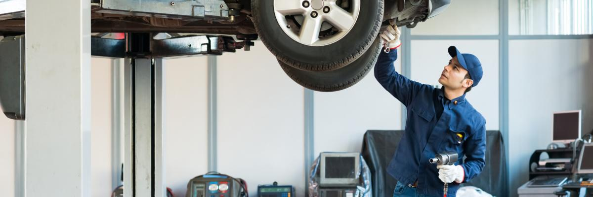 mechanic working in garage with vehicle on a lift, mechanic working on vehicle suspension